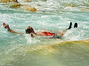 """A swimmer in Little Colorado River in Grand Canyon National Park, Arizona, USA. Downstream of Blue Spring, the Little Colorado River glows brilliant turquoise due to suspension of minerals including calcium carbonate, seen on Day 4 of 16 days rafting 226 miles down the Colorado River in Grand Canyon National Park. Marble Canyon runs from Lees Ferry at River Mile 0 to the confluence with the Little Colorado River at Mile 62, which marks the beginning of the Grand Canyon. Although John Wesley Powell knew that no marble was found here when he named Marble Canyon, he thought the polished limestone looked like marble. In his words, """"The limestone of the canyon is often polished, and makes a beautiful marble. Sometimes the rocks are of many colors – white, gray, pink, and purple, with saffron tints."""""""