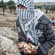 A young palestinian demonstrator is holding  stones near the  separation wall erected by Israel. Bil'in, Westbank - May 13th 2011.
