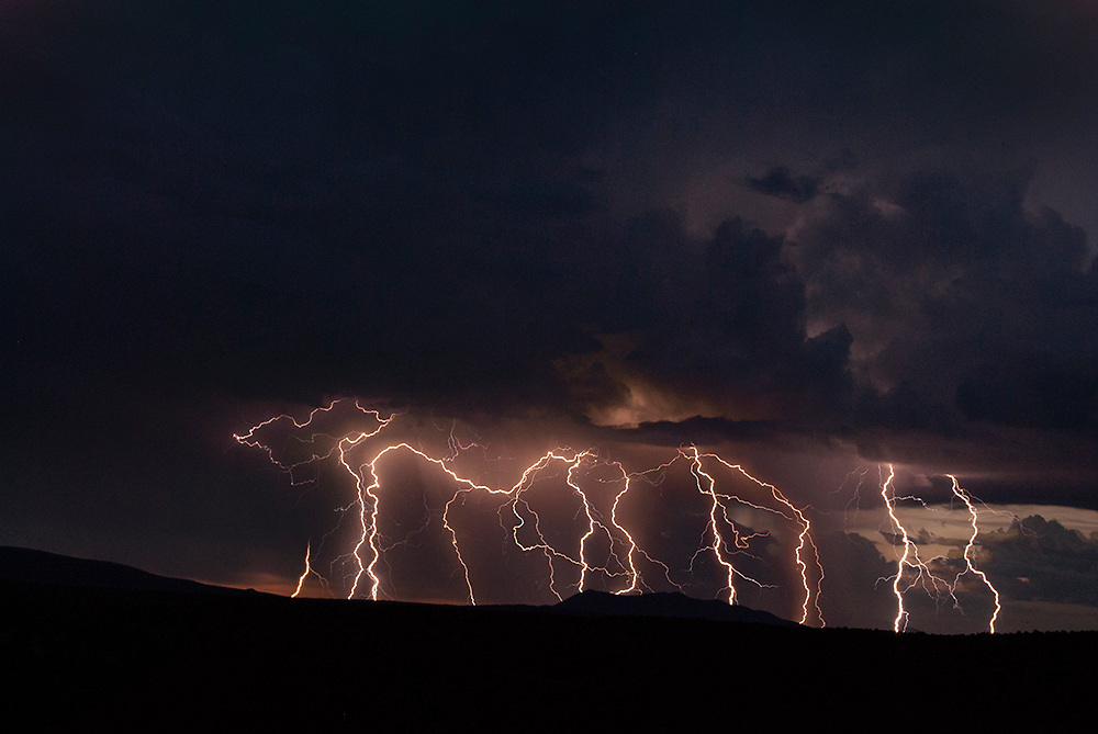 """A fine art photograph of multiple lightning strikes at sunset over El Rio Grande del Norte National Monument. New Mexico. USA.<br /> <br /> AVAILABLE AS:<br /> <br /> Size 20"""" x 16"""" (50.8cm x 40.6cm approx)*<br /> Edition of ONLY 100 at this size.<br /> US$350 + shipping<br /> <br /> Hand printed in Taos, New Mexico, USA by Taos Print and Photography Services using archival inks and fine art paper. signed and numbered by hand.<br /> <br /> Contact jim@jimodonnellphotography.com to order"""