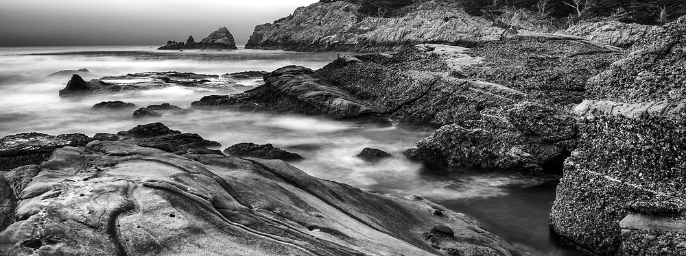 Waves of the Pacific Ocean crash against the rocky shores of Headland Cove at Point Lobos. Carmel, CA. Point Lobos holds a special place in the history of photography. It's fog-enshrouded shores were a subject of photographers such as Edward Weston, Ansel Adams and Minor White.