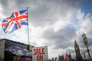 A Union Jack flag flies above the Houses of Parliament and a tourist trinket kiosk where a Sale On sign suggests that Britain is a victim of the Brexit referendum to leave the EU, on 12th September 2017, in London, England.