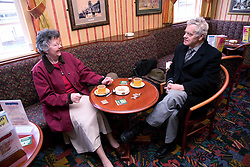 Older couple chatting over a cup of coffee in a pub,