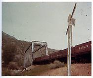 Train of D&RGW drop-bottom gondolas crossing river on a through-truss bridge.<br /> D&RGW
