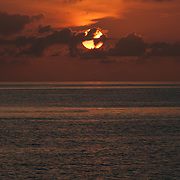 As it descends to the horizon, the sun is partially covered by some thin clouds. Taken at Swains Reef on the southern end of the Great Barrier Reef of the coast of Queensland, Australia.