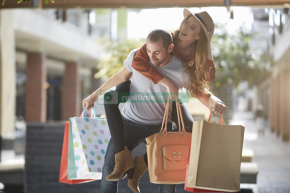 Jan. 13, 2015 - Man carrying woman on back, holding shopping bags (Credit Image: © Image Source/Image Source/ZUMAPRESS.com)