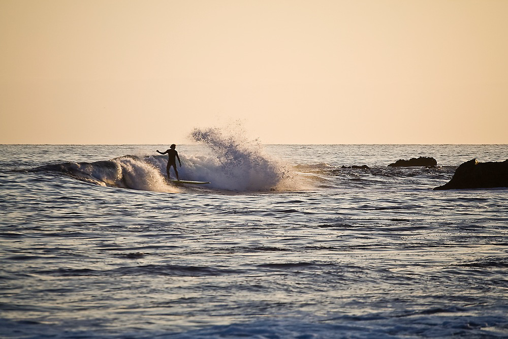 A surfer stands up on his surfboard, catching a wave off of Laguna Beach, California.
