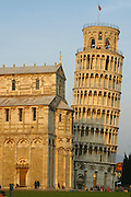 The leaning Tower of Pisa and the Baptistery catch the sun at sunset, Campo dei Miracoli, Pisa, Italy.