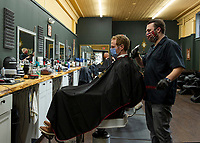 """Ross Bartlett gets a long overdue haircut from Sam """"Harvard"""" Ferrante at Polished and Proper on Monday afternoon.  (Karen Bobotas/for the Laconia Daily Sun)"""