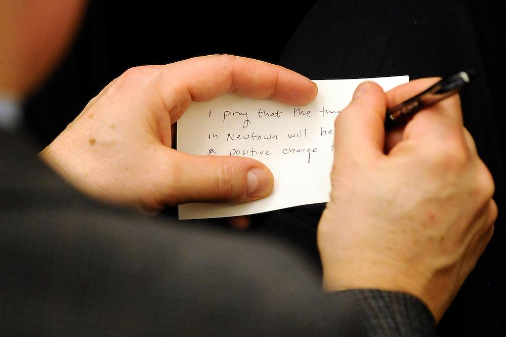 A man writes a prayer for Newtown on a note card during an interfaith sermon at Newtown Congregational Church in Newtown, Conn., Sunday, Jan. 20, 2013.(AP Photo/Jessica Hill)