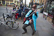Rock band comprised of middle aged men, street busking and entertaining people on Brick Lane London, UK. The bass player wearing a blue Teddy Boy jacket provides some amusement with his lewd gestures.