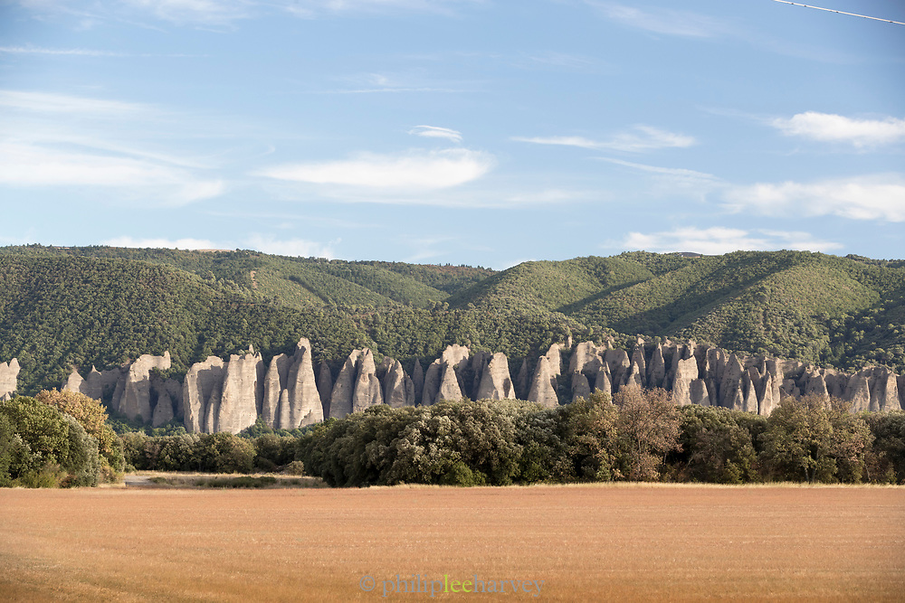 Les Penitents de Mees rock formation perching over field and forest, Les Mees, France