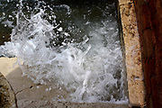 Water from the canal spraying up against the stone wall 2013. in venice, Italy.
