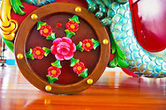 At Nunley's Carousel, closeup of carved chariot wheel decorated with pink red flowers, from level of wood floor platform, at Museum Row, Garden City, New York, USA, on August 7, 2012