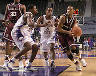 Texas A&M guard Acie Law (R) drives into the lane against pressure from Kansas State's Clent Stewart (C) and Cartier Martin (L) during the first half of K-State's 58-54 win over the Aggies at Bramlage Coliseum in Manhattan, Kansas, January 18, 2006.