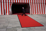 A Corporation worker inspects the red carpet and red and white striped marquee after a military event at the Guildhall in the City of London, the capital's financial district and historic heart. Stepping across the red space, the employee looks for imperfections although there are boot marks on the end  many people have already walked over the material. The Guildhall has been an important centre for City of London affairs since the twelfth century. 800 years on, Guildhall is still home of the City of London Corporation, and acts as a grand setting for glittering banquets in honour of visiting Heads of State and other dignitaries, royal occasions, and receptions for major historical anniversaries.