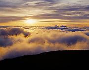 Sunrise above clouds viewed from Pu'u 'Ula'ula Overlook, Red Hill, highest point on Maui at 10,023 feet, edge of Haleakala Crater, Haleakala National Park, Hawaii.
