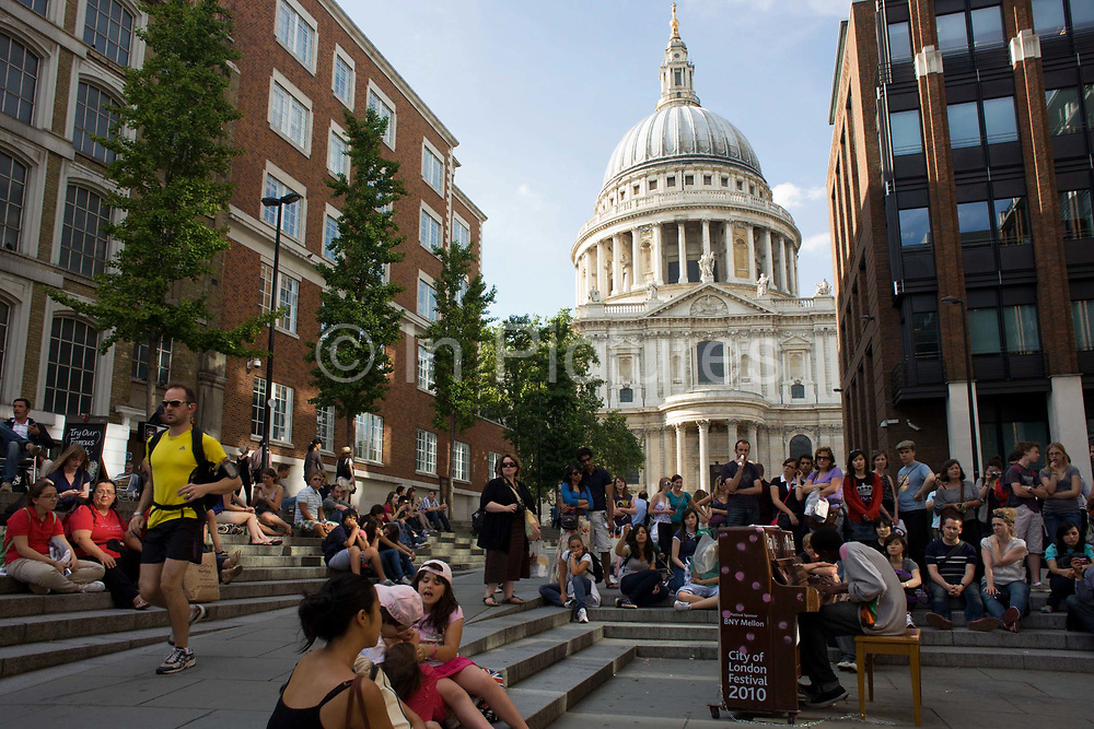 When nearby offices have emptied on such a warm summer's afternoon, crowds of local workers and tourists sit on the steps between offices both old and new and beneath the towering dome of St. Paul's Cathedral. Entertaining the people is a lone pianist, playing an upright piano as part of City of London's play a piano music festival. Anyone able to play can simply sit on the stool and play the instrument as the feel like it and passers-by can enjoy unsung talents. A jogger dressed in yellow runs past but otherwise, those listening to the impromptu music sit with appreciative respect for the young black man, hunched over the keys.