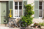 Typical street scene quaint house with shutters and bicycle, traditional architecture, St Martin de Re, Ile de Re, France