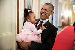 President Barack Obama holds the daughter of former staff member Darienne Page Rakestraw in the Cross Hall of the White House, April 3, 2015. (Official White House Photo by Pete Souza)<br /> <br /> This official White House photograph is being made available only for publication by news organizations and/or for personal use printing by the subject(s) of the photograph. The photograph may not be manipulated in any way and may not be used in commercial or political materials, advertisements, emails, products, promotions that in any way suggests approval or endorsement of the President, the First Family, or the White House.