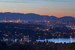 United States, Washington. Lake Washington, Mercer Island, Seattle skyline, and Olympic mountains viewed from Bellevue at sunset.