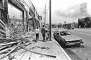 A group of children walk on a sidewalk on Adams Blvd. past several burned down businesses. .Los Angeles has undergone several days of rioting due to the acquittal of the LAPD officers who beat Rodney King..Hundreds of businesses were burned to the ground and over 55 people have been killed.