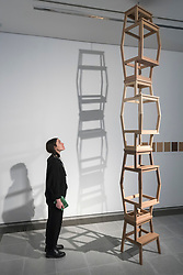 "© Licensed to London News Pictures. 03/03/2020. LONDON, UK. A staff member poses next to a tower of replicas of IKEA step stools made from seven different species of wood. Preview of ""Cambio"" by Formafantasma, an Italian design duo based in Amsterdam.  The exhibition is an ongoing investigation into the governance of the timber industry and takes place at the Serpentine Sackler Gallery 4 March to 17 May 2020.  Photo credit: Stephen Chung/LNP"