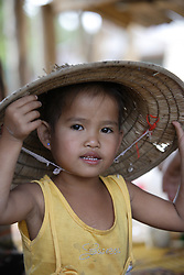 Lang wearing her mothers traditional broad-rimmed hat used to keep the sun off when she is in the fields.<br /> Lang is 5 years old today, January 16th 2010.  Lang's mother Bounlid was photographed in the 6 months before giving birth and each year for the following 5 years following the birth, for the WHO Great Expectations project. <br /> Huey Kham Village, Santhong District, Vientiane Province, Lao PDR