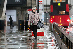 © Licensed to London News Pictures. 01/12/2018. London, UK.  A woman waits for a bus near London Bridge station during rain and wet weather on the first day of meteorological winter.  Photo credit: Vickie Flores/LNP