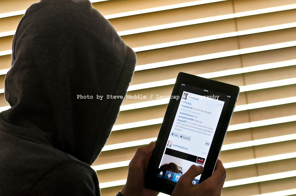 Teenage Boy Viewing Social Media Website Using Ipad - Apr 2013.