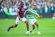 Arnaud Djoum (#10) of Heart of Midlothian holds off Scott Sinclair(#11) of Celtic FC during the Betfred League Cup semi-final match between Heart of Midlothian FC and Celtic FC at the BT Murrayfield Stadium, Edinburgh, Scotland on 28 October 2018.