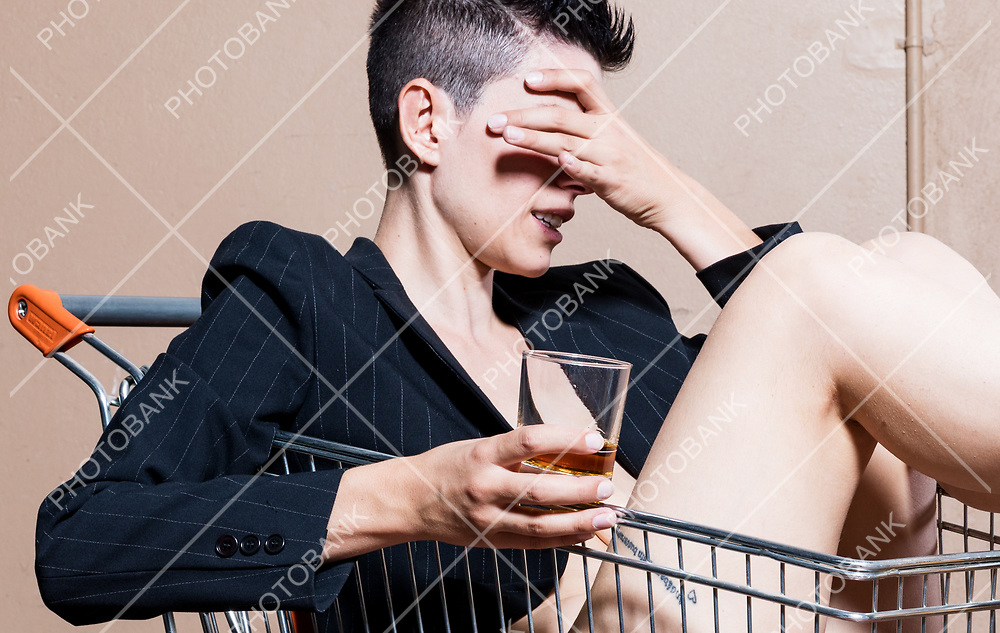 Woman sitting in a shopping cart is hiding the visono with a glass of cognac in her hand. She is half naked