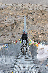 Tattoo artist Justin Big Meas Wilson riding a Royal Enfield Himalayan across a suspension bridge in Motorcycle Sherpa's Ride to the Heavens motorcycle adventure in the Himalayas of Nepal. On the fifth day of riding, we went from Muktinath to Tatopani. Friday, November 8, 2019. Photography ©2019 Michael Lichter.