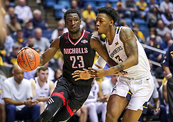 Dec 14, 2019; Morgantown, WV, USA; Nicholls State Colonels forward Elvis Harvey Jr. (23) drives baseline while defended by West Virginia Mountaineers forward Gabe Osabuohien (3) during the first half at WVU Coliseum. Mandatory Credit: Ben Queen-USA TODAY Sports