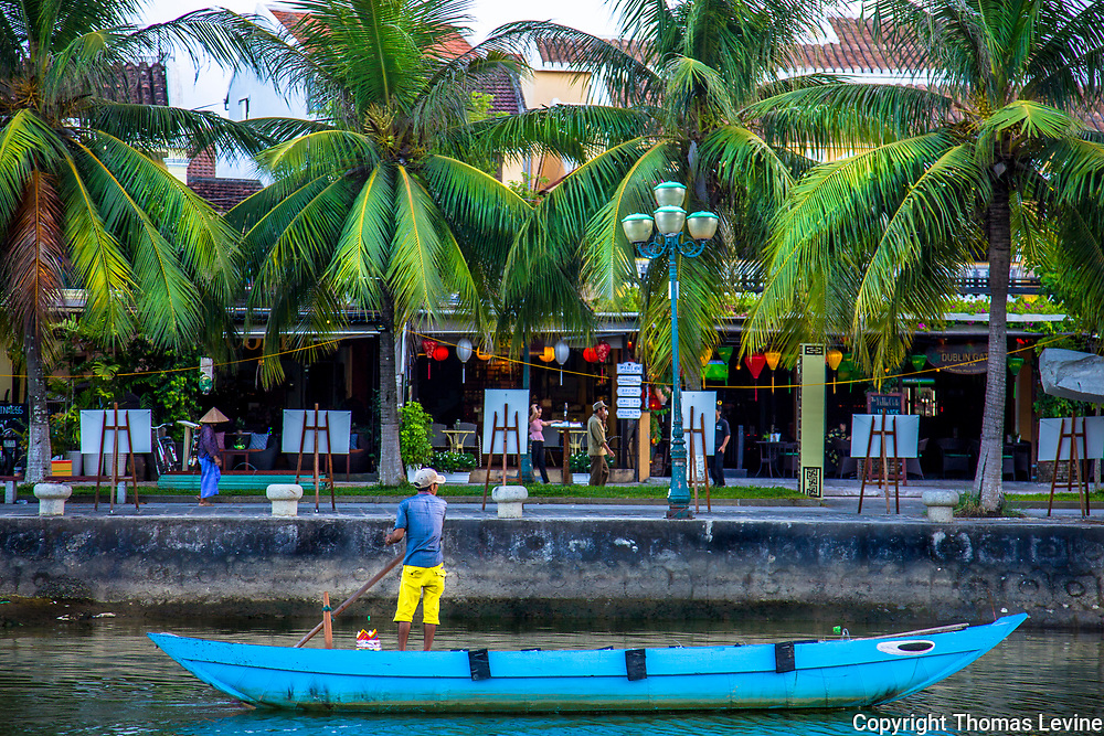 Fine Art:<br /> Late day colors pop with blue boat and man with a pole in his boat. The background has vivid green palm trees in front of Hoi An store fronts.