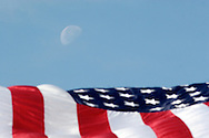 Middletown, NY - The moon is seen over a large American flag set up for the Middletown-Wallkill Veterans Council Memorial Day ceremonies and parade on May 26, 2008. The flag was hanging from two fire department ladder trucks.