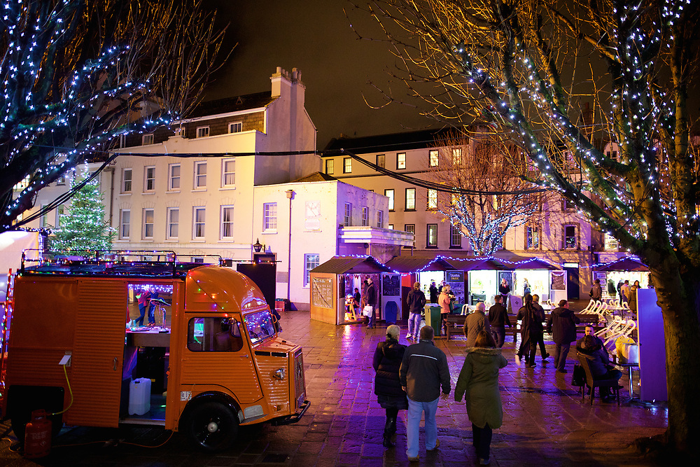 Fete de Noue market in the Royal Square, Jersey lit up by Christmas lights in the trees