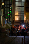 Evening crowds of drinkers stand beneath the modernity of the Lloyds of London headquarters in the Square Mile, the heart of the capital's historical financial district, on 2nd October 2017, in the City of London, England.
