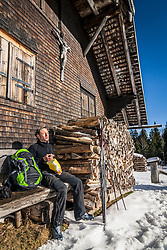 Man Taking rest on bench in front of a log cabin