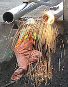 A welder cuts a section of pipe for a temporary viaduct support beam. (Steve Ringman / The Seattle Times, 2008)
