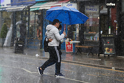 © Licensed to London News Pictures. 10/09/2021. London, UK. Couple shelter from the rain underneath an umbrella in north London, as wet weather conditions continue after a recent mini heatwave in London. Photo credit: Dinendra Haria/LNP