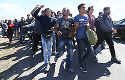 © London News Pictures. Migrants run to try and escape being contained by police close to the Hungarian and Serbian border town of Roszke, Hungary, September 7 2015. The UN's humanitarian agencies are on the verge of bankruptcy and unable to meet the basic needs of millions of people because of the size of the refugee crisis in the Middle East, Africa and Europe, senior figures within the UN have told the media.   Picture by Paul Hackett /LNP