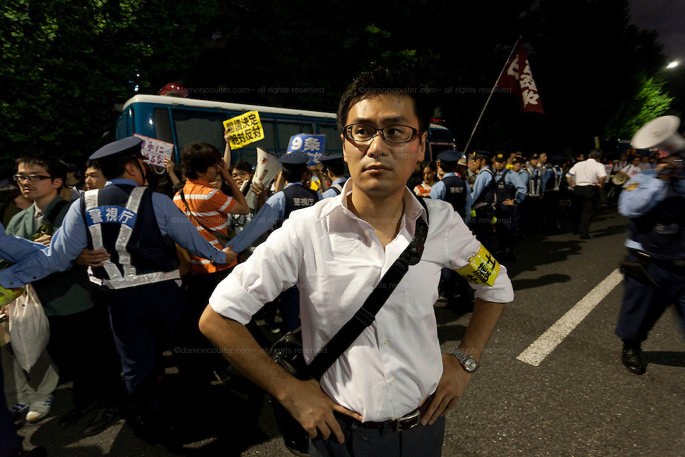 A lawyer checks the actions of the police at a protest against the revision of article 9 of the Japanese Constitution outside the Prime-Minister's house in Kasumigasaki, Tokyo, Japan. Monday June 30th 2014. Over 10,000 people showed their support for Japan's unique peace constitution and called on the government to halt its reinterpretation of Article 9 allowing Collect Self Defence which is expected to become law on July 1st