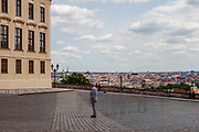 """A man standing at empty """"Hradcany Square"""" (Hradcanske Namesti) towards the panoramic view at the Prague cityscape. On the left Prague Castle. The Czech government lowered the security measures and as of Monday 25 May 2020, wearing of protective masks will be mandatory only in the interiors of buildings other than the place of residence and in public transport."""