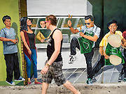05 JUNE 2015 - KUALA LUMPUR, MALAYSIA:  A tourist walks past a mural on a wall near the Kuala Lumpur Central Market, historically one of the most important markets in KL. Now it has been turned into a tourist handicraft market and food court.    PHOTO BY JACK KURTZ