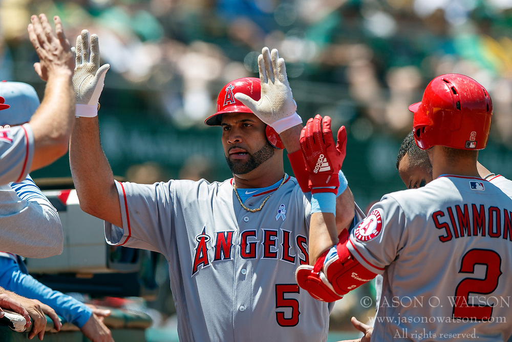 OAKLAND, CA - JUNE 17: Albert Pujols #5 of the Los Angeles Angels of Anaheim is congratulated by teammates after hitting a home run against the Oakland Athletics during the sixth inning at the Oakland Coliseum on June 17, 2018 in Oakland, California. The Oakland Athletics defeated the Los Angeles Angels of Anaheim 6-5 in 11 innings. (Photo by Jason O. Watson/Getty Images) *** Local Caption *** Albert Pujols