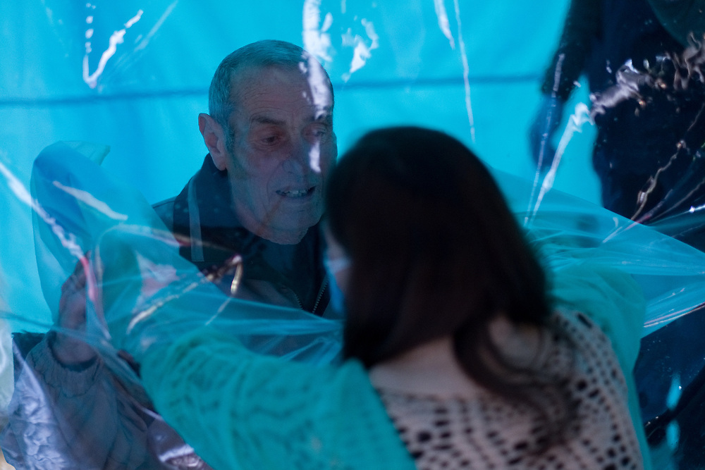 A woman wearing a protective suit against the spread of the novel coronavirus COVID-19 meets a relative through a plastic sheet installed in a special 'hug room' organised to keep people safe from COVID-19 infection at a care home in Santa Lucia di Serino, province of Avellino, southern Italy, on January 2, 2021.