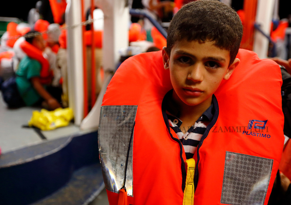 A migrant child on the Migrant Offshore Aid Station (MOAS) ship MV Phoenix wait to be transferred to the Norwegian ship Siem Pilot off the coast of Libya August 6, 2015.  An estimated 700 migrants on an overloaded wooden boat were rescued 10.5 miles (16 kilometres) off the coast of Libya by the international non-governmental organisations Medecins san Frontiere (MSF) and MOAS without loss of life on Thursday afternoon, according to MSF and MOAS, a day after more than 200 migrants are feared to have drowned in the latest Mediterranean boat tragedy after rescuers saved over 370 people from a capsized boat thought to be carrying 600.<br /> REUTERS/Darrin Zammit Lupi <br /> MALTA OUT. NO COMMERCIAL OR EDITORIAL SALES IN MALTA