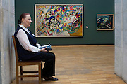 """Moscow, Russia, 27/04/2011..An attendant sits in front of Kandinsky's """"Composition Vll"""" & """"Lake"""" in the Tretyakov Gallery, the foremost depository of Russian fine art in the world, in the gallery's collections of early Twentieth Century Russian art."""