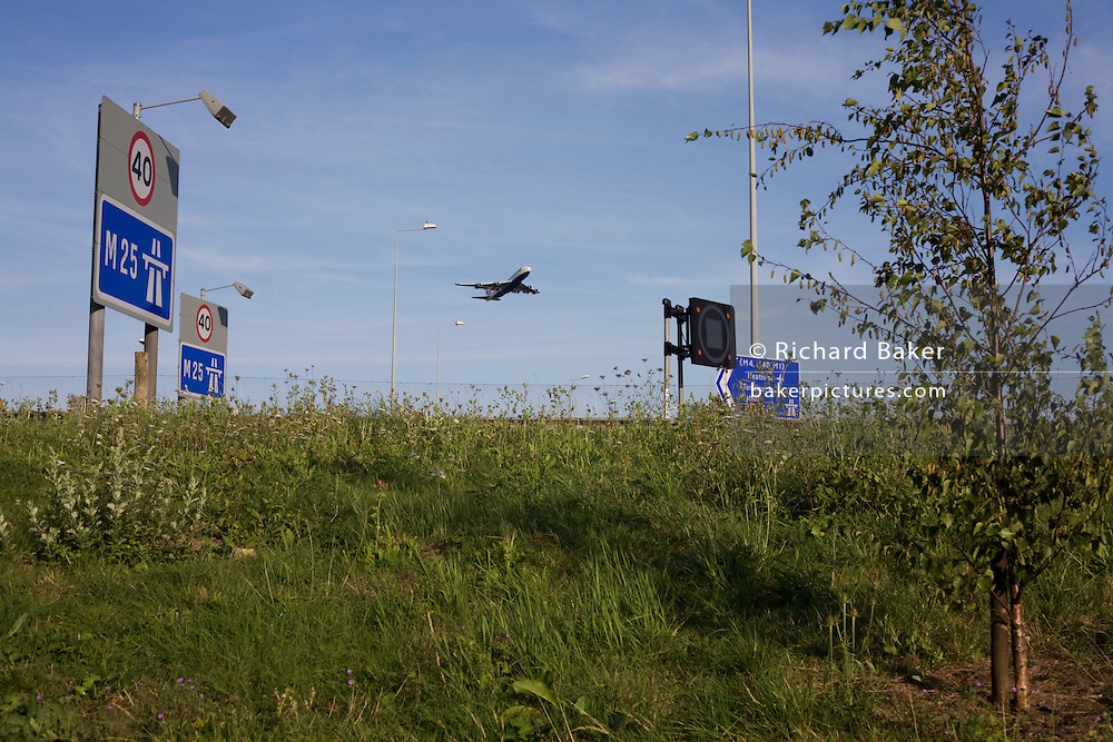 A passing airliner that passes overhead on a flight-path from Heathrow airport over M25 at Poyle on Colne Valley Way.