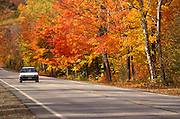 Image of a car driving on a road in the White Mountains National Forest near Franconia Notch in the fall, New Hampshire, American Northeast by Randy Wells